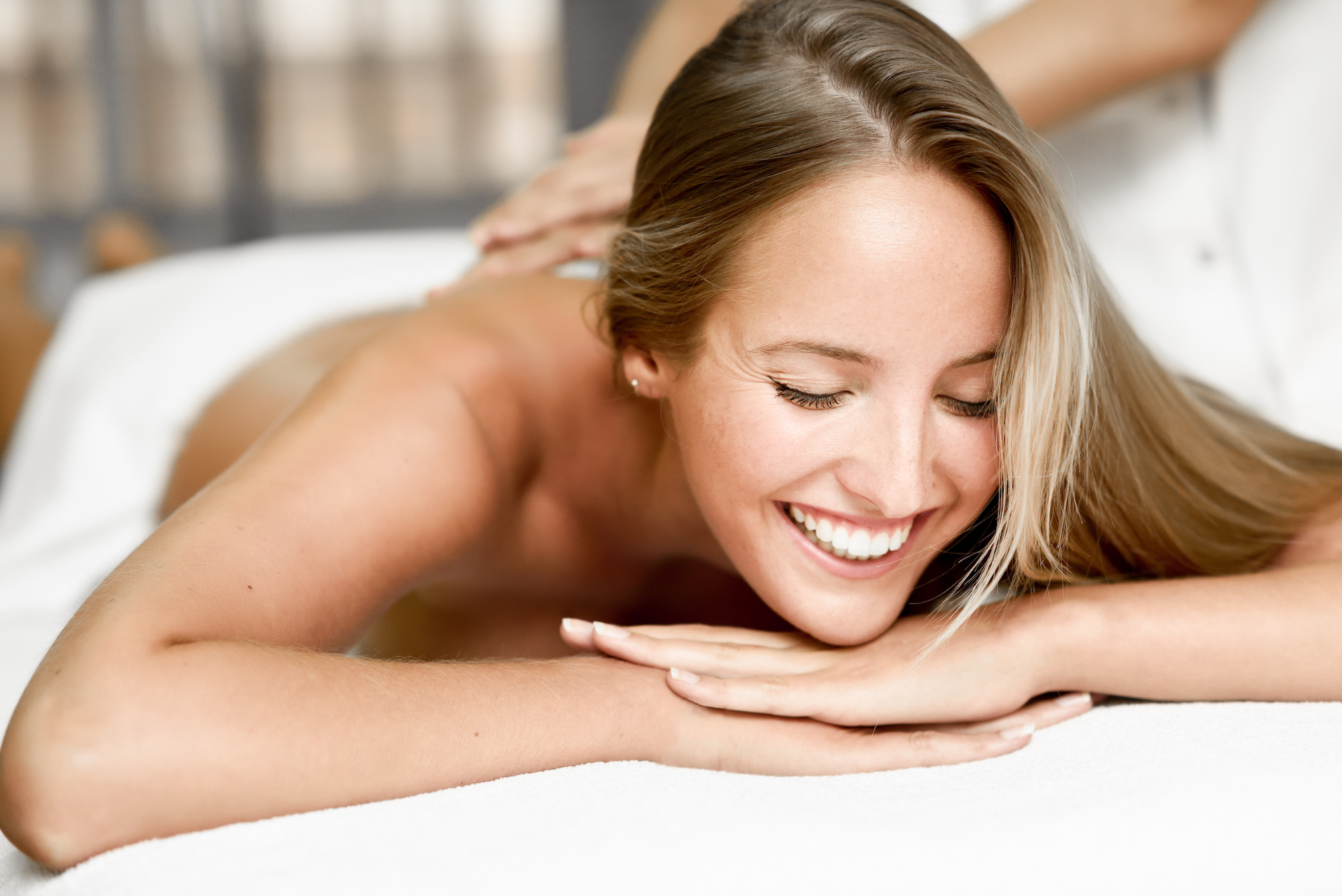 Young blond woman having massage in the spa salon. Massage and body care. Body massage treatment. Smiling female.